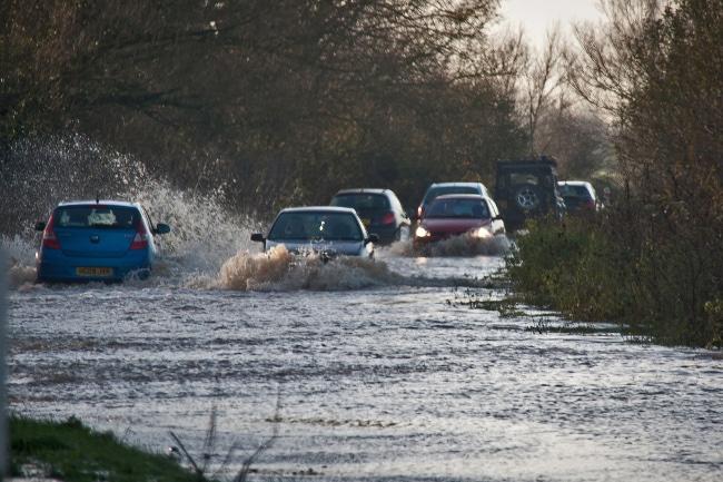 Cars drive through a flood near Taunton. Image