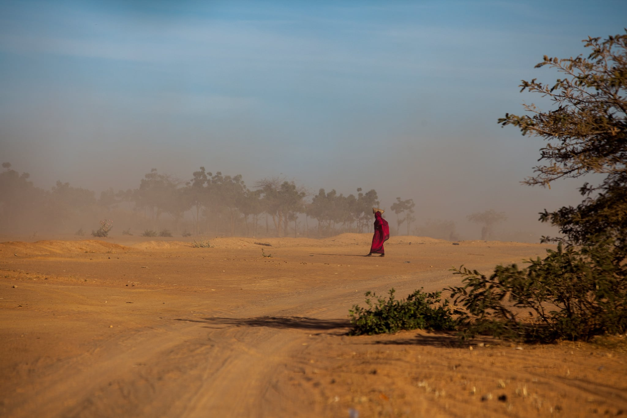 Woman walks along a dusty dirt road in Chad